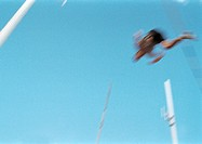 Male pole vaulter in mid-air, blurred motion
