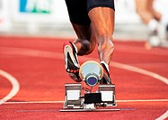 Male runner leaving starting block, low section