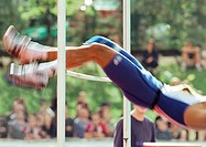 Male high jumper clearing bar