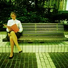 Businesswoman sitting on bench, reading file