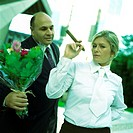 Businessman holding flowers, woman holding cigar, portrait