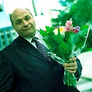 Businessman holding flowers, portrait (thumbnail)