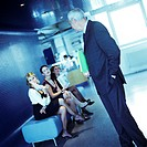 Mature businessman looking at three young women