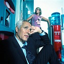 Mature businessman sitting on ground, young woman behind standing next to water cooler
