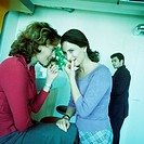 Two young women whispering, man in background