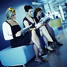 Three young women sitting, reading newspapers, side view