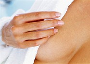 Woman covering breast with bathrobe, focus on hand and breast