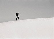 Man hiking across dune, side view, b&amp;w