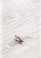 Four men rowing crew in boat, elevated view, blurred