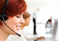 Woman wearing headset in office, side view, close-up