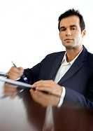 Businessman sitting at desk, blurred, portrait