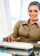 Businesswoman with hand on keyboard, smiling, portrait (thumbnail)