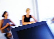 Women sitting at desk, blurred
