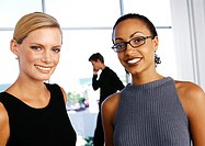 Businesswomen smiling, man talking on phone in background
