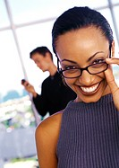 Businesswoman lowering glasses and smiling, man using phone in background, portrait
