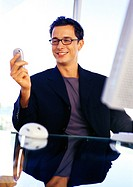 Businessman holding cell phone, smiling