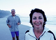 Mature man and woman in sportswear on beach