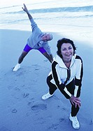 Mature man and woman stretching on beach