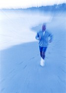 Mature man running on beach, blurred