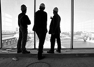 Three men wearing hard hats, looking out of window, rear view, b&w