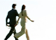 Businessman and woman walking, rear view, blurred