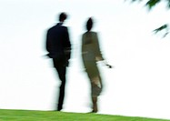 Businessman and woman walking on grass, rear view, blurred