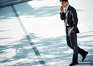 Businessman walking outdoors with cell phone