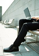 Man on bench with laptop computer on knees, close-up