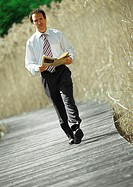 Businessman walking with newspaper in hands, outdoors, portrait