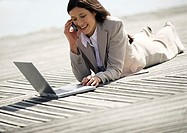 Businesswoman lying with laptop computer outdoors