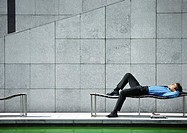 Businessman lying on bench outdoors