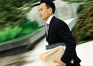 Businessman hurrying, outdoors, blurred