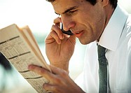 Businessman using cell phone and looking at newspaper, close-up, side view