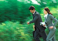Businessman and woman running in park, blurred