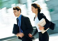 Businessman and woman walking outdoors, blurred motion