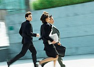 Business people running outdoors, blurred motion