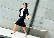 Businesswoman using cell phone and walking, blurred