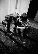 Two children on stairs, one holding head in hands, b&amp;w