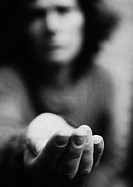 Woman holding hand out, blurred, b&w