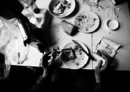 Hands holding food on dirty table, b&amp;w