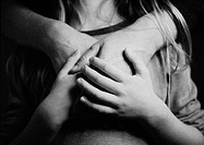 Hands against child's chest, close-up, b&amp;w