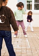 Three children playing hopscotch