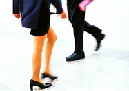 Businessman and businesswoman walking, low section
