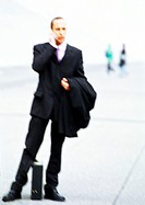 Businessman with briefcase in hand, using cell phone