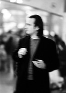 Businessman holding cell phone, blurred, b&w