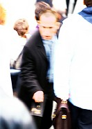 Businessman in crowd with briefcase in hand, blurred