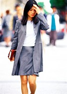 Businesswoman walking with book in hand (thumbnail)