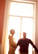 Woman and man standing in front of window, blurred, tilt