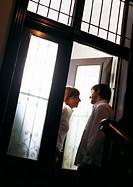 Man talking to woman in doorway, tilt