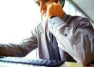 Businessman on cell phone, working at computer, partial view, close-up